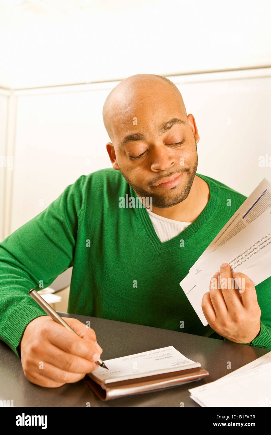 African man writing check - Stock Image