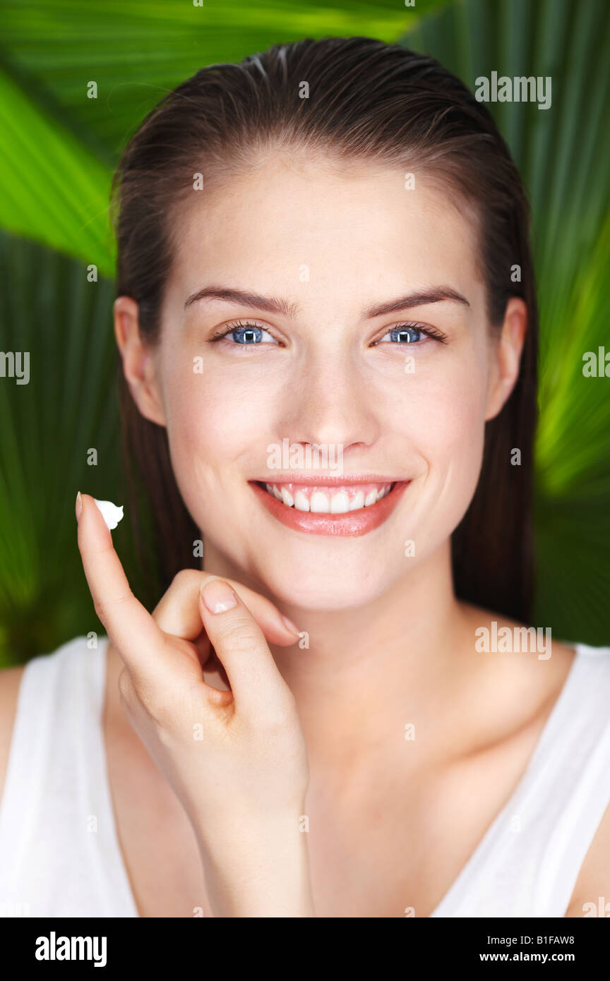 Portrait of young woman with sun cream on her finger - Stock Image