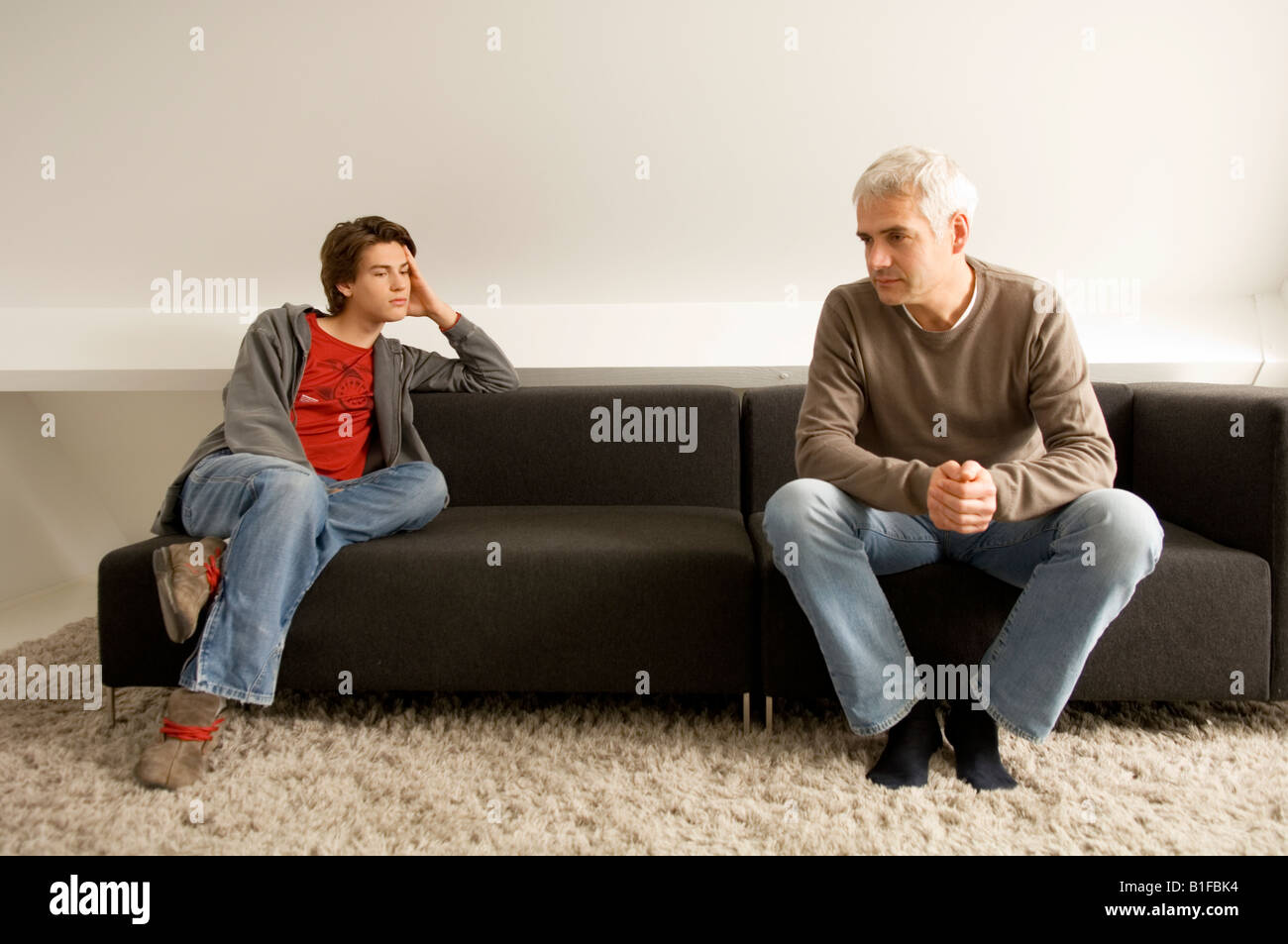 Mature man and his son sitting on a couch - Stock Image