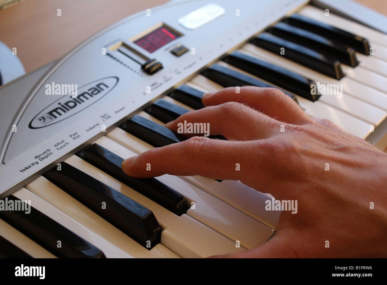 Hand playing keyboard - Stock Image