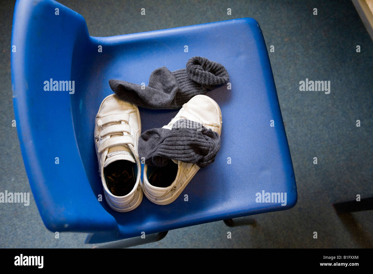 Childu0027s Socks And Shoes Abandoned On A Blue School Chair