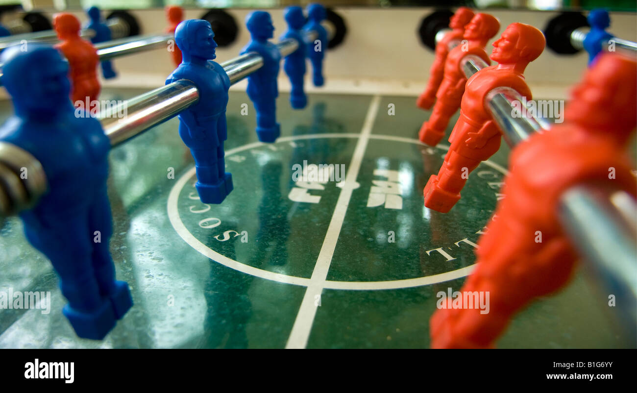 Close up of table football game, red and blue teams. - Stock Image