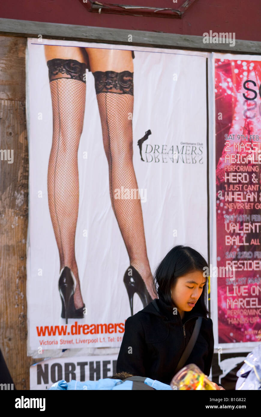 Chinese street vendor with poster in background showing fishnet clad legs advertising pole dancing club - Stock Image