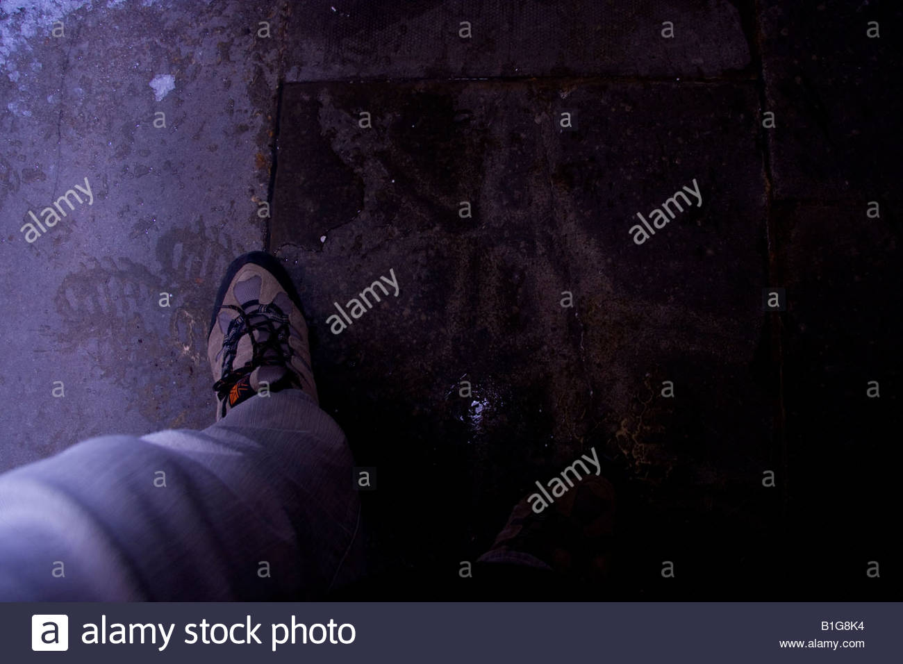 Foot emerging out of the darkness at night time, eerie and creepy, menacingly - Stock Image