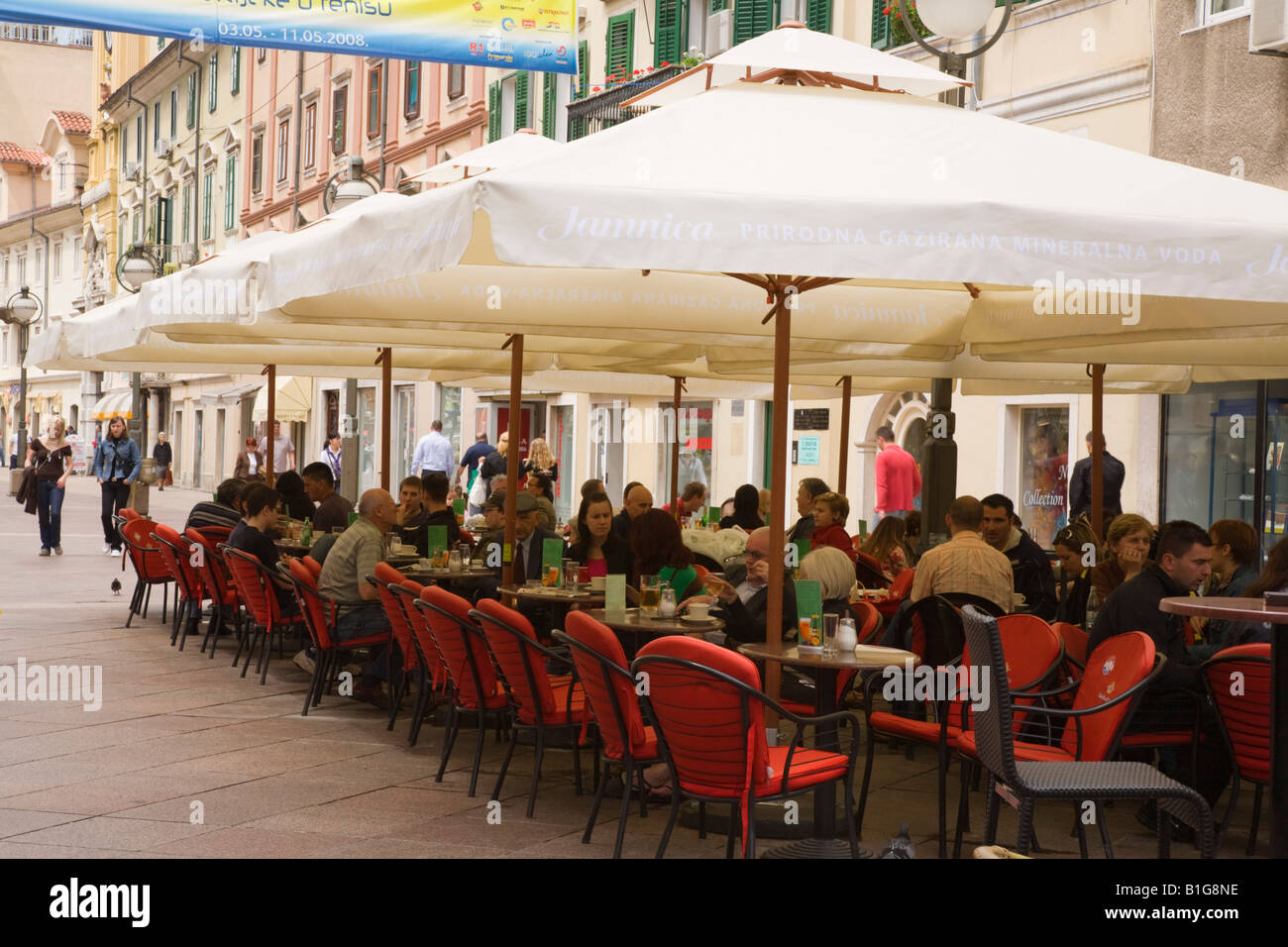People Dining And Drinking Under Sun Umbrellas In Outdoor Cafe In Stock Photo Alamy