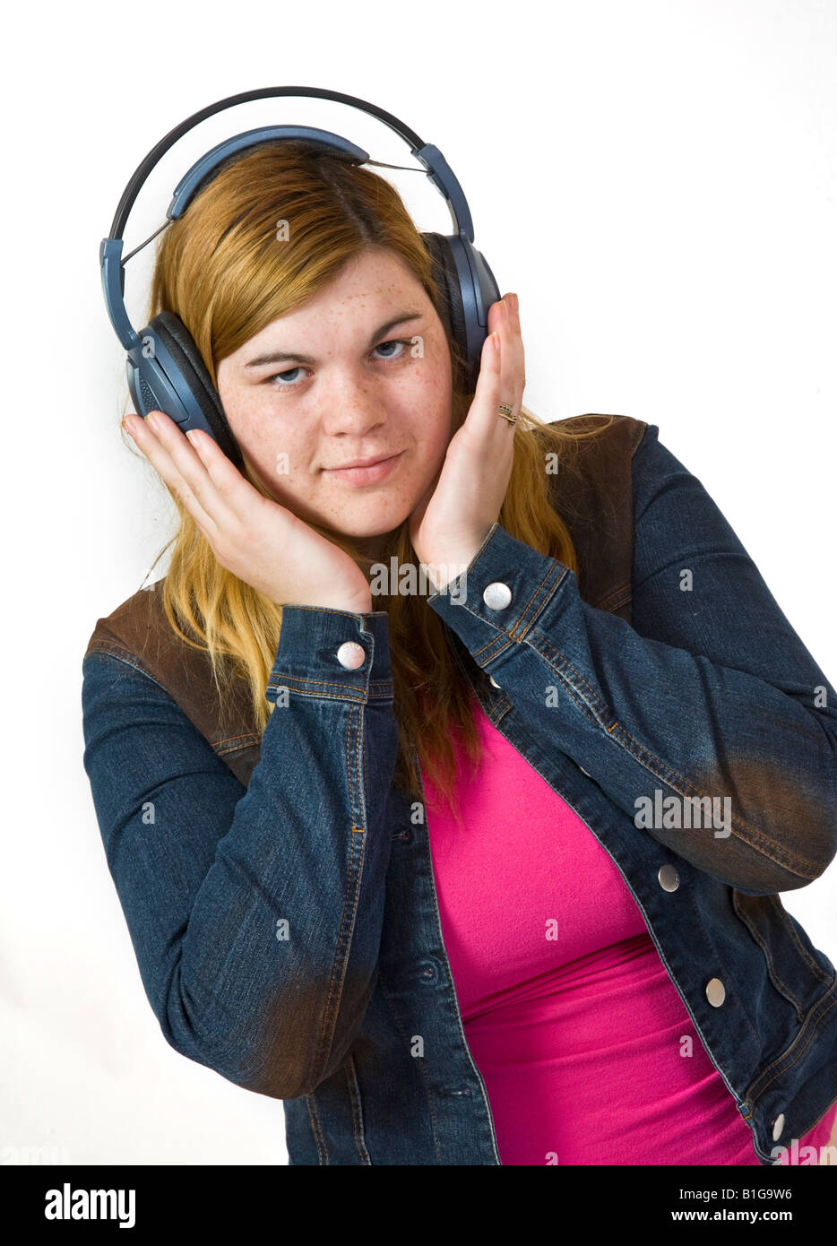 Young woman listens to music on headphones. - Stock Image