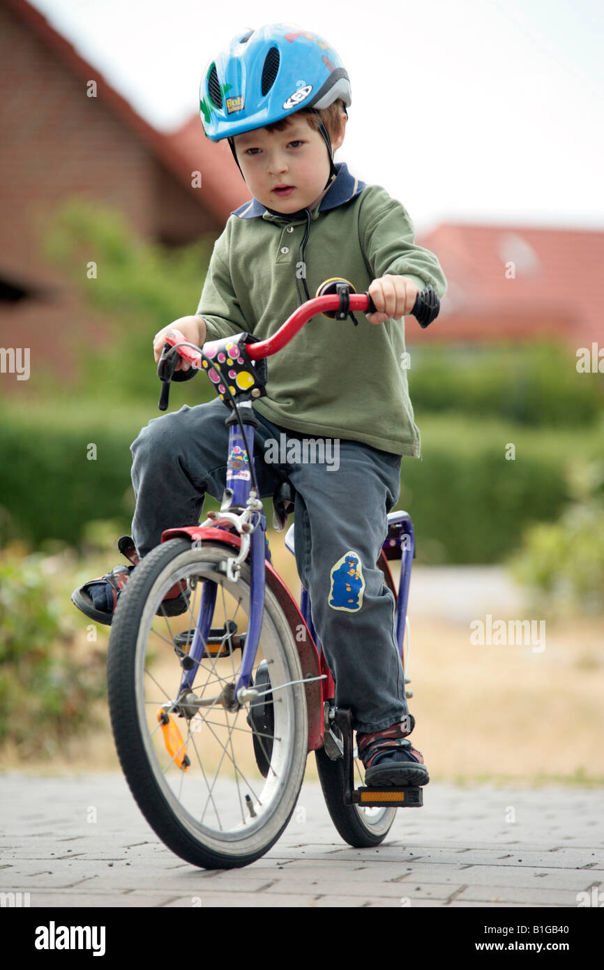 young boy on a juvenile bicycle - Stock Image