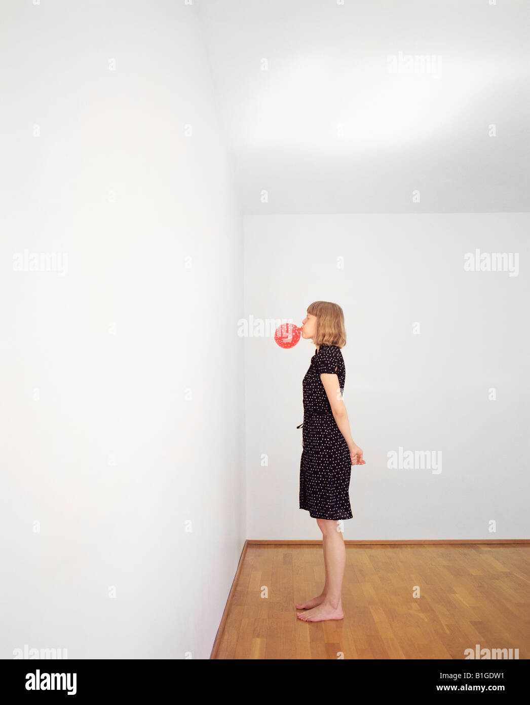 Side profile of a young woman blowing a balloon - Stock Image