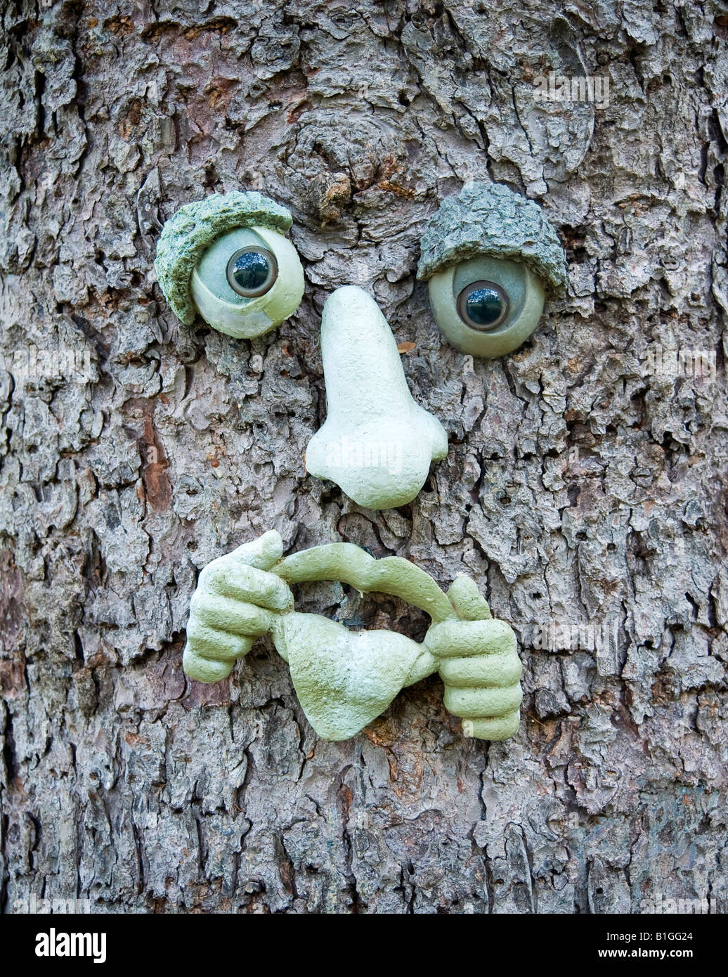 artistic ceramic face parts on pine tree bark - Stock Image