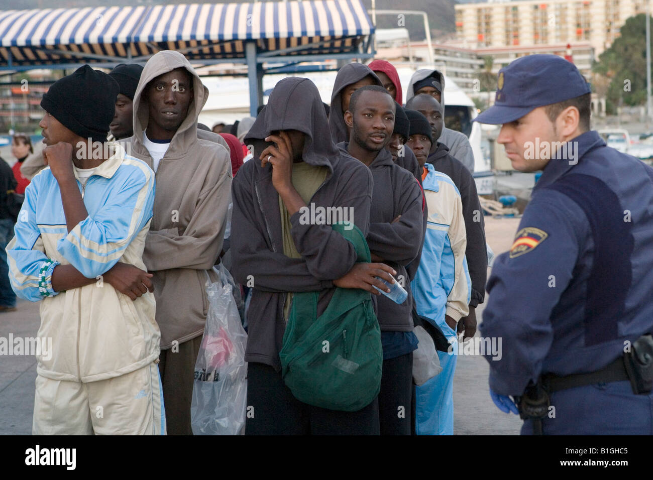 African refugees and a spanish police man - Stock Image