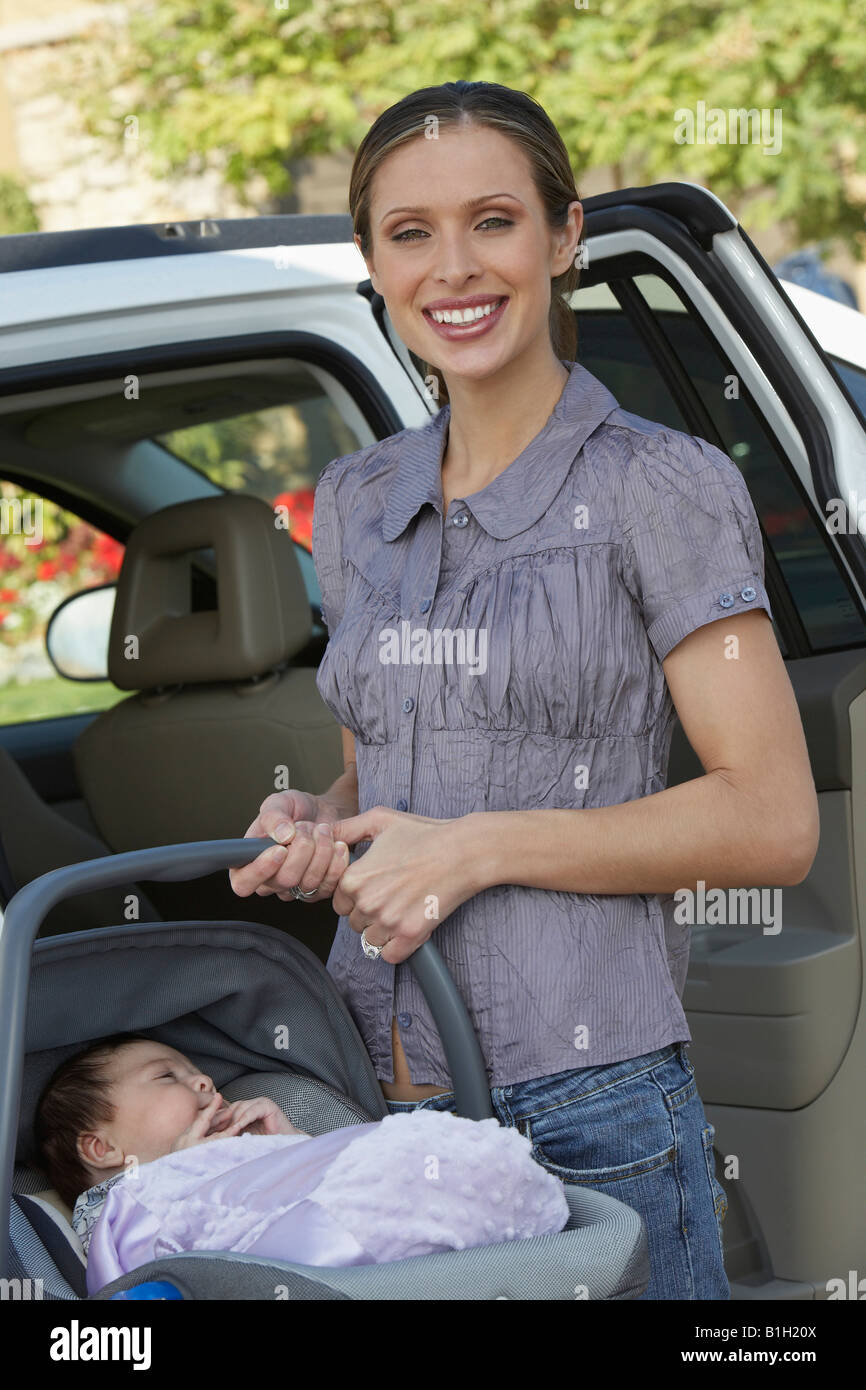 Portrait of woman with baby (1-6 months) in carrier by car - Stock Image