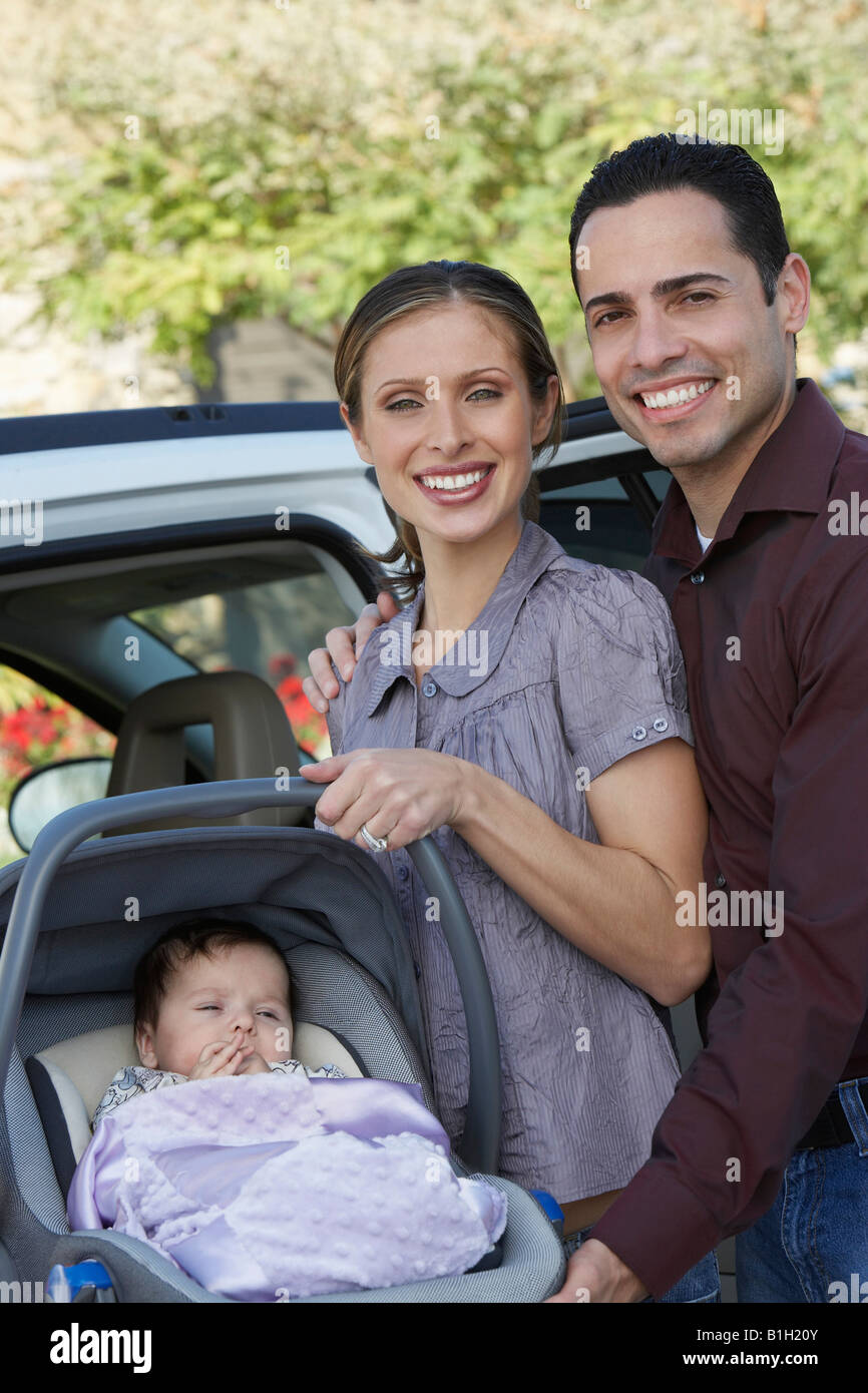 Portrait of couple with baby (1-6 months) in carrier by car - Stock Image