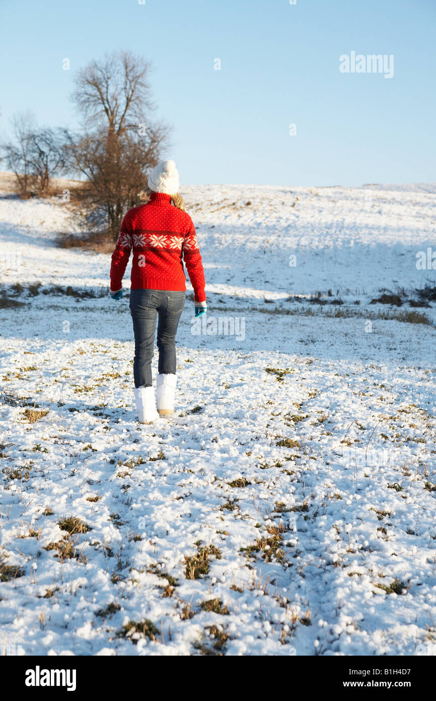 Woman walking on snowy ground - Stock Image