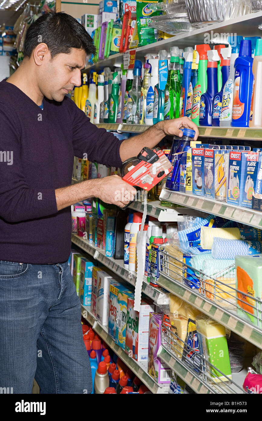 Man in shop with price gun - Stock Image