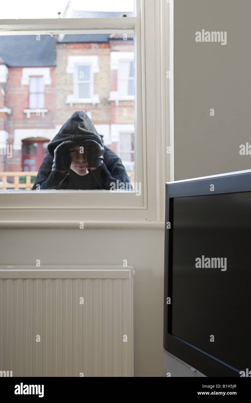 Burglar looking through window - Stock Image