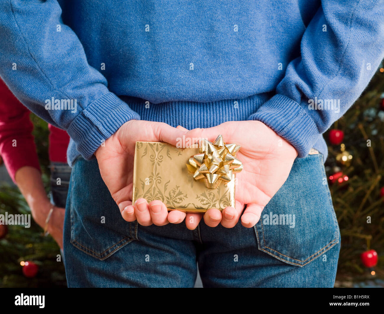 Man hiding a christmas present behind back - Stock Image