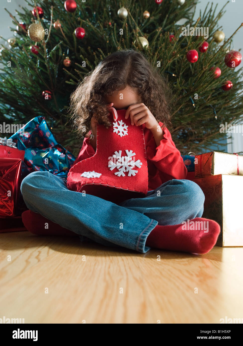 Girl looking in a christmas stocking - Stock Image