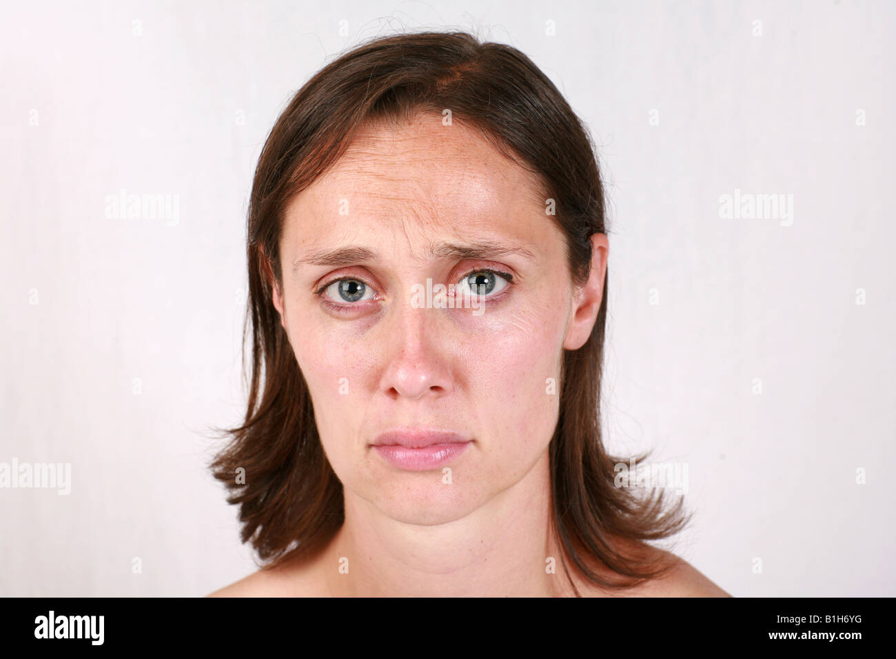 Young brunette woman head shot closeup with sad upset despondent depressed down dispirited low somber facial expression - Stock Image