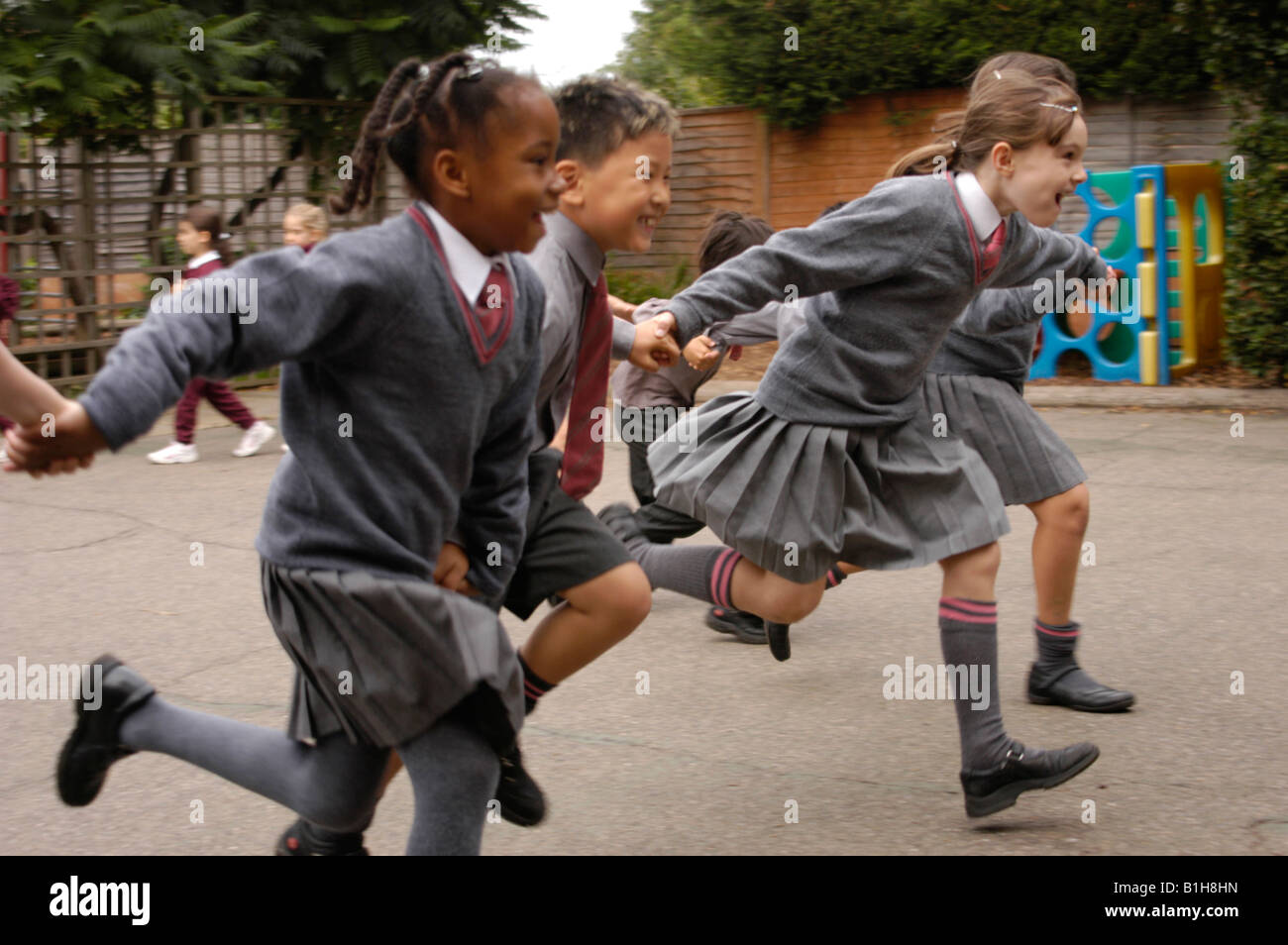 group of children running in the playground of a private school - Stock Image