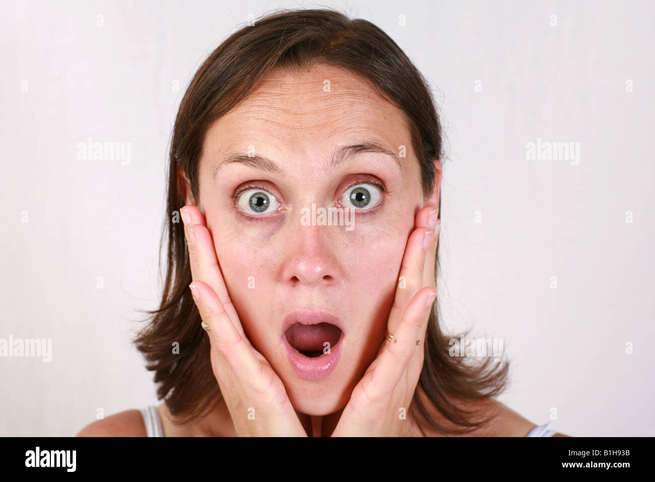 Young brunette open mouthed brunette woman holds head in hands looking shocked stunned amazed aghast surprised - Stock Image
