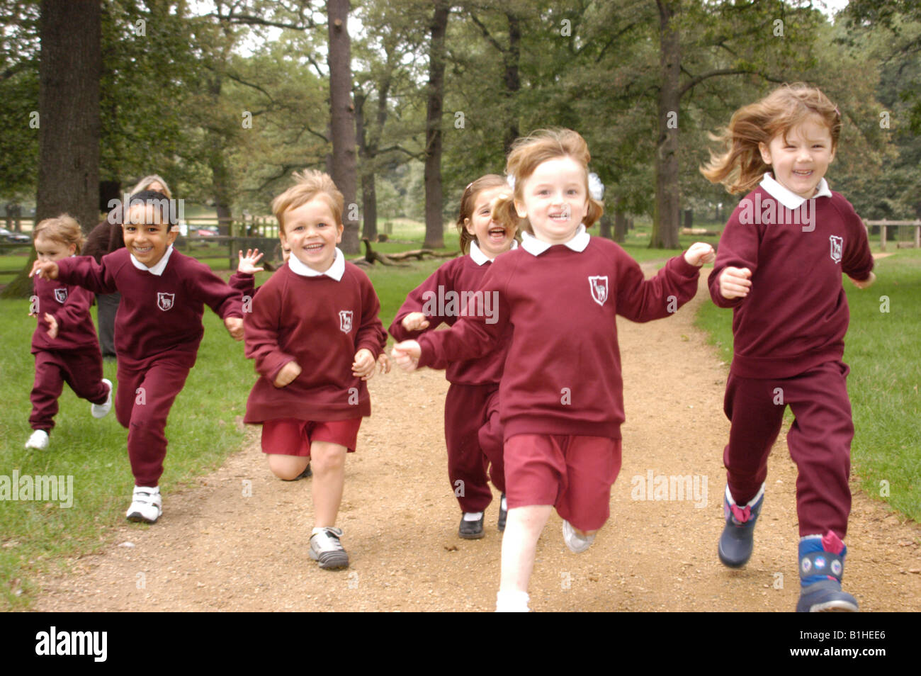 School children running through a park - Stock Image
