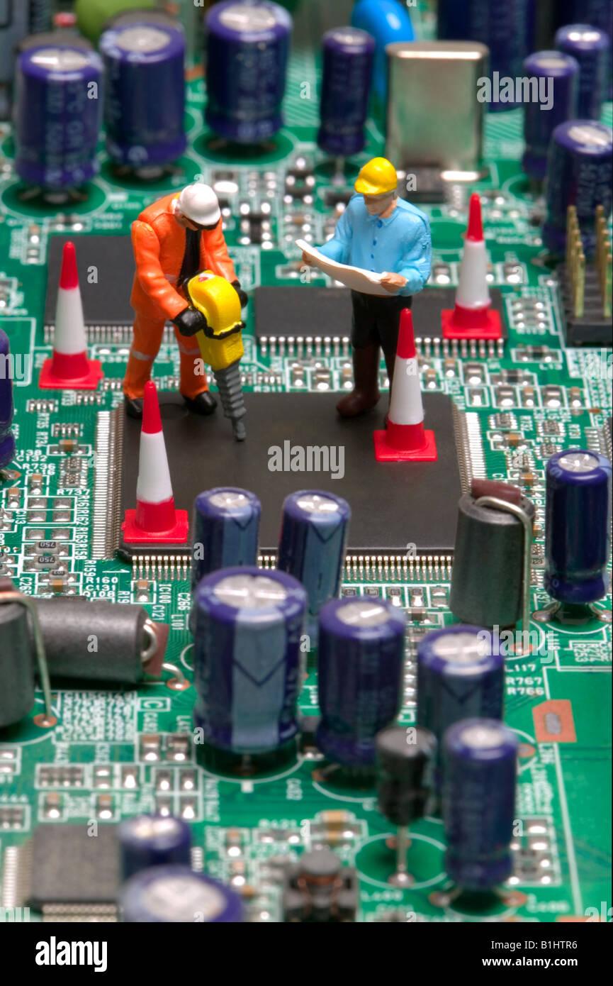Mini workmen repairing a broken circuitboard - Stock Image