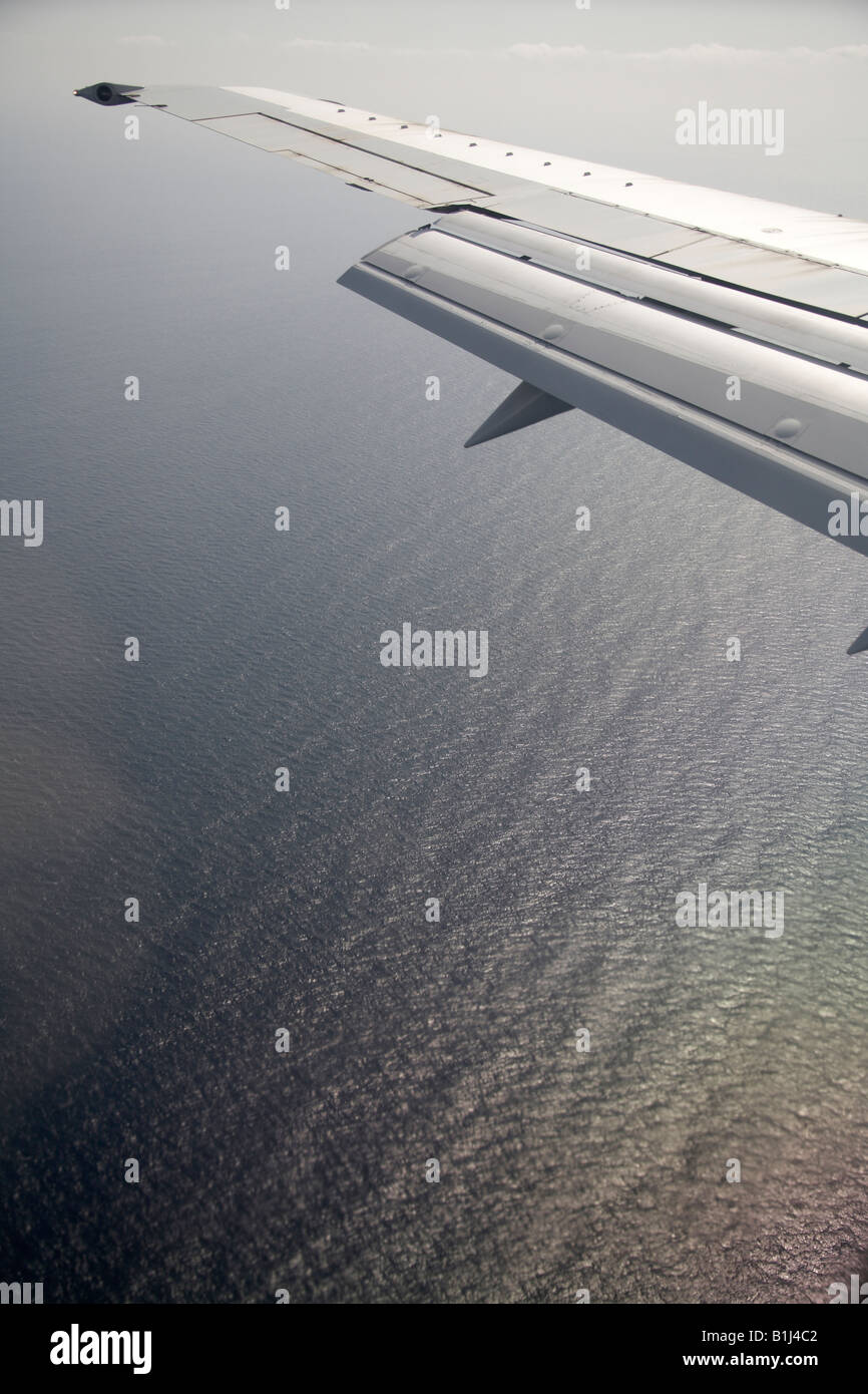 High level oblique aerial view of aircraft wing flying over sea - Stock Image