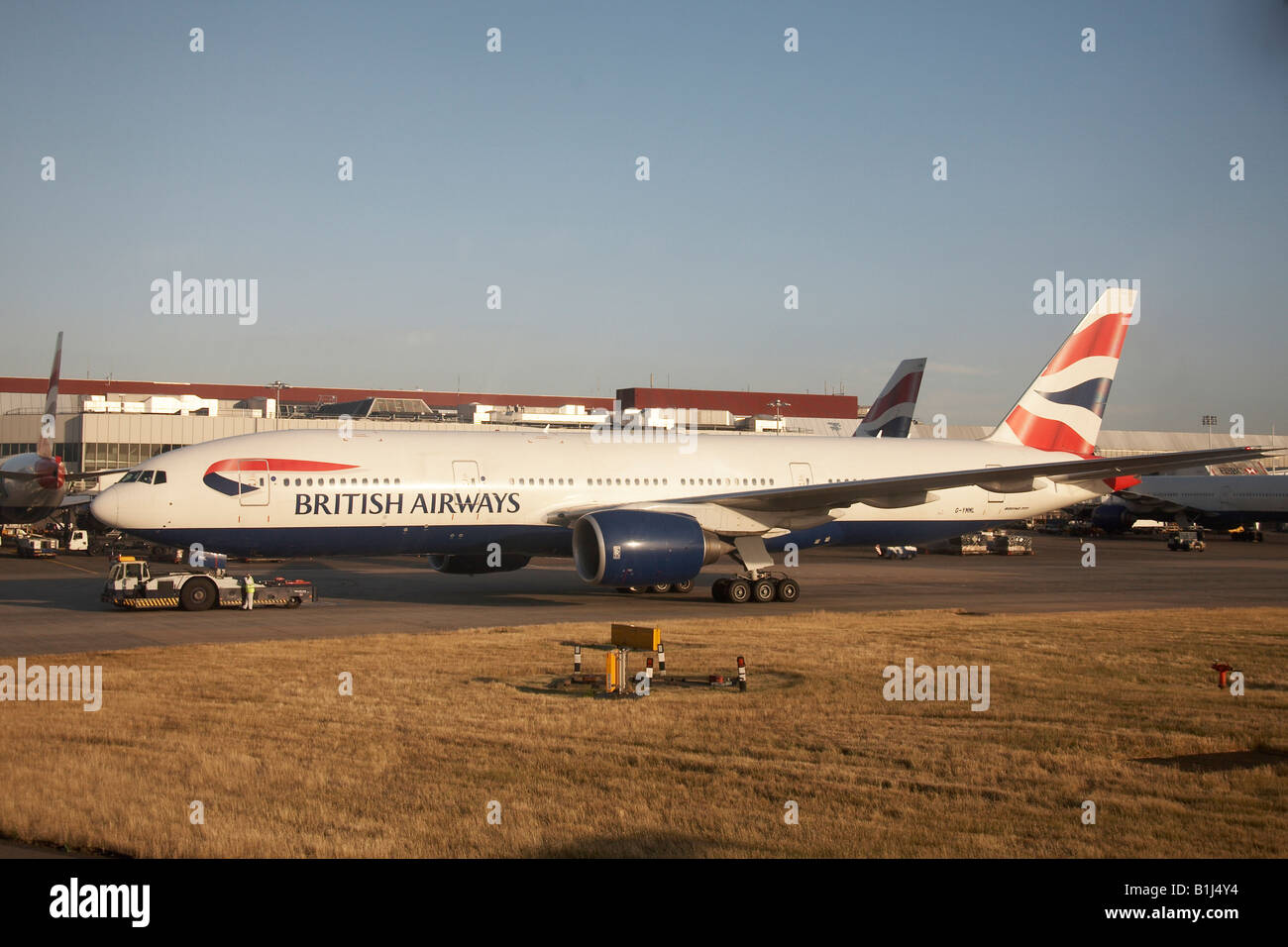 Boeing 777 G YMML British Airways taxiing on apron at Heathrow Airport London TW6 England High level oblique - Stock Image