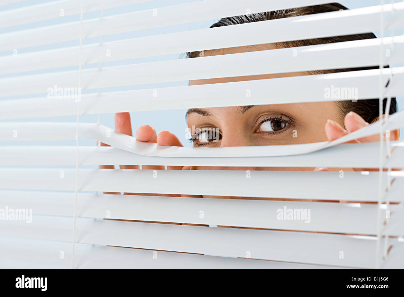 Woman looking though blinds - Stock Image