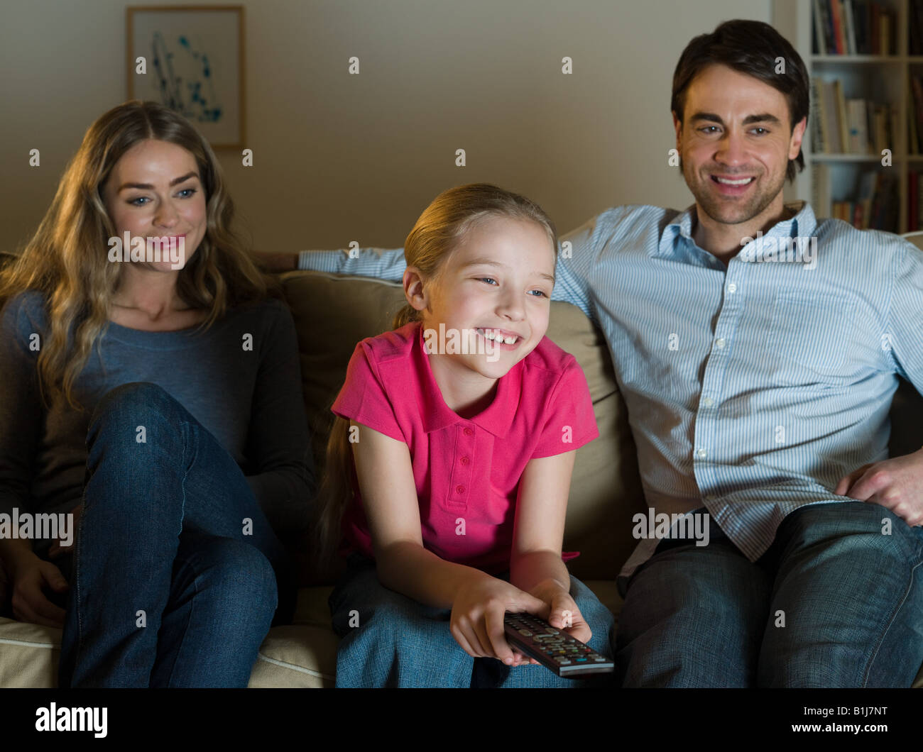 Parents watching tv with their daughter - Stock Image