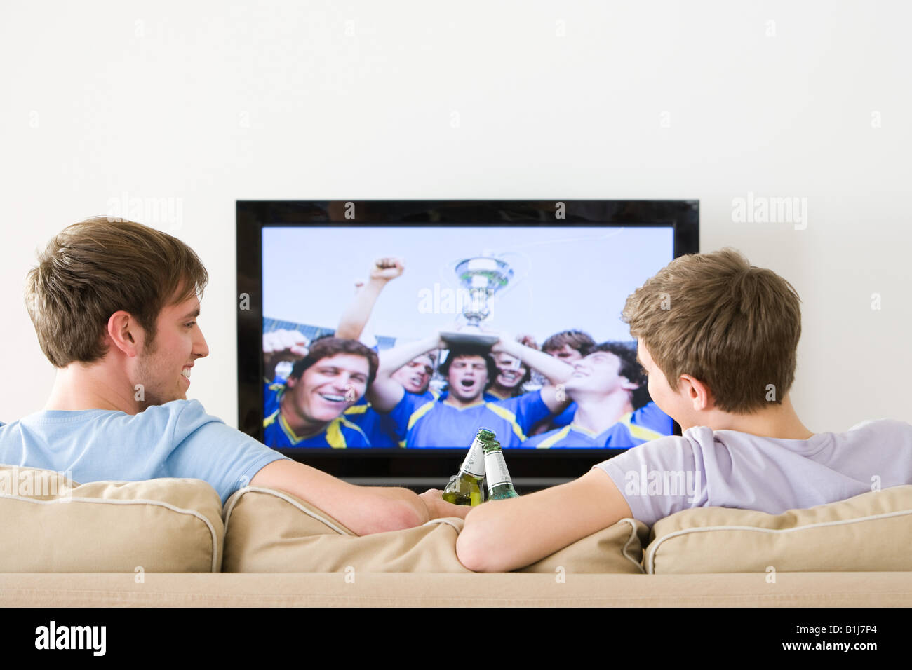 Two young men watching football on the tv - Stock Image