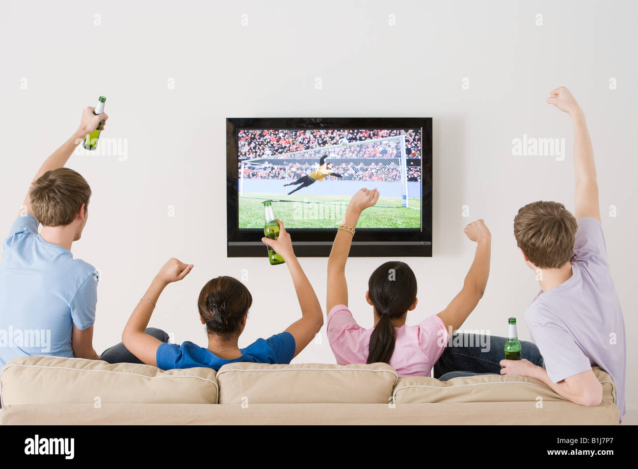 Friends watching football on the tv - Stock Image