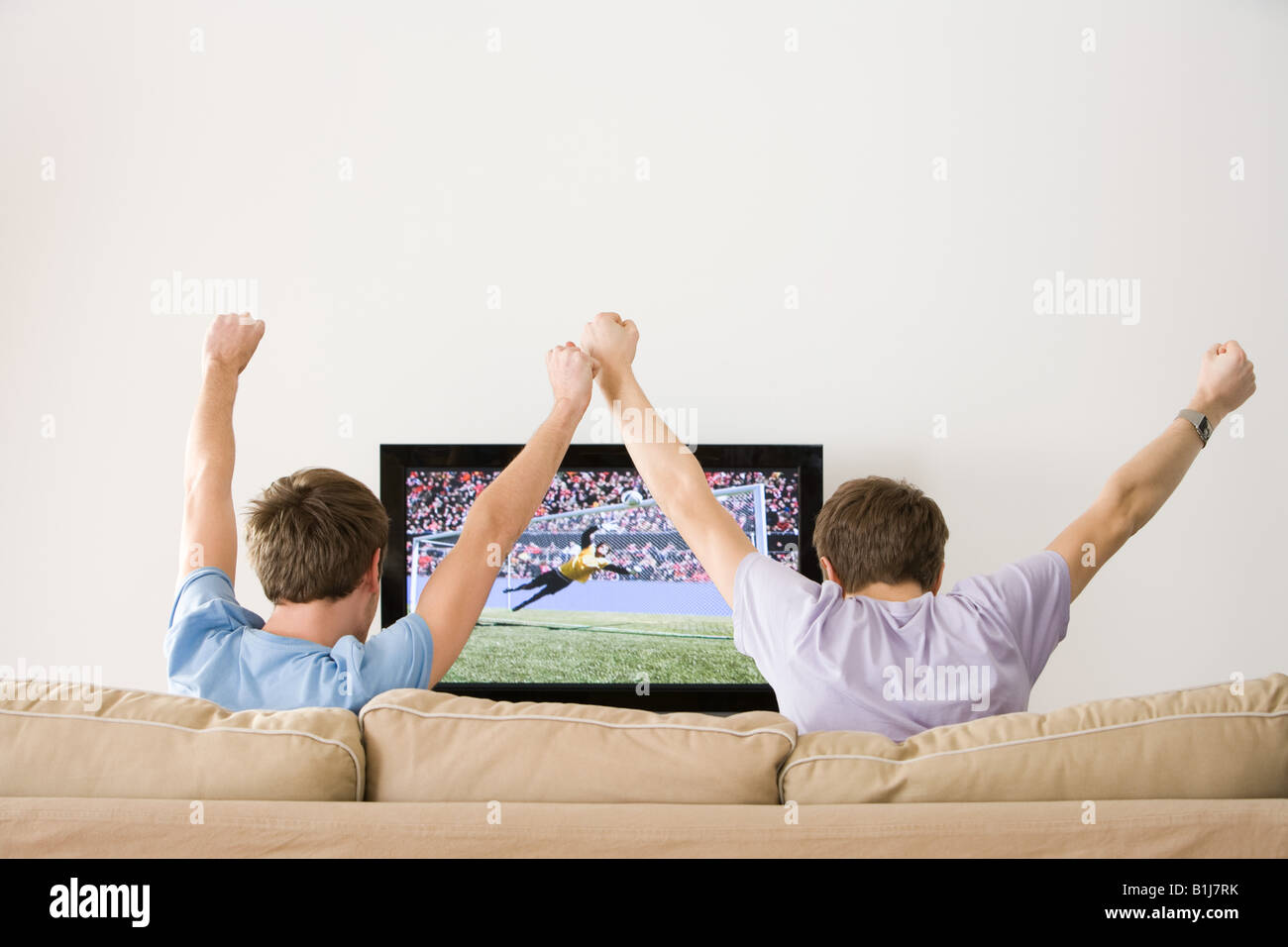 Two young men cheering at football on the tv - Stock Image