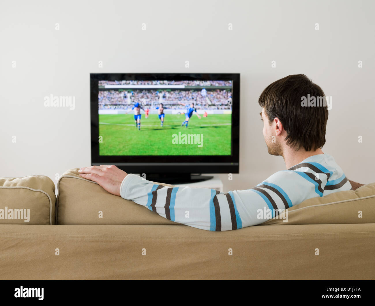 A man watching a football match on the tv - Stock Image