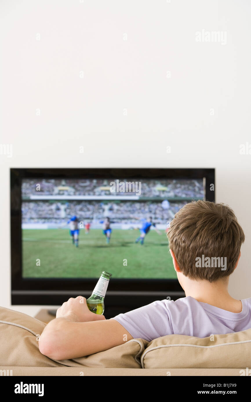 A young man watching a football match - Stock Image