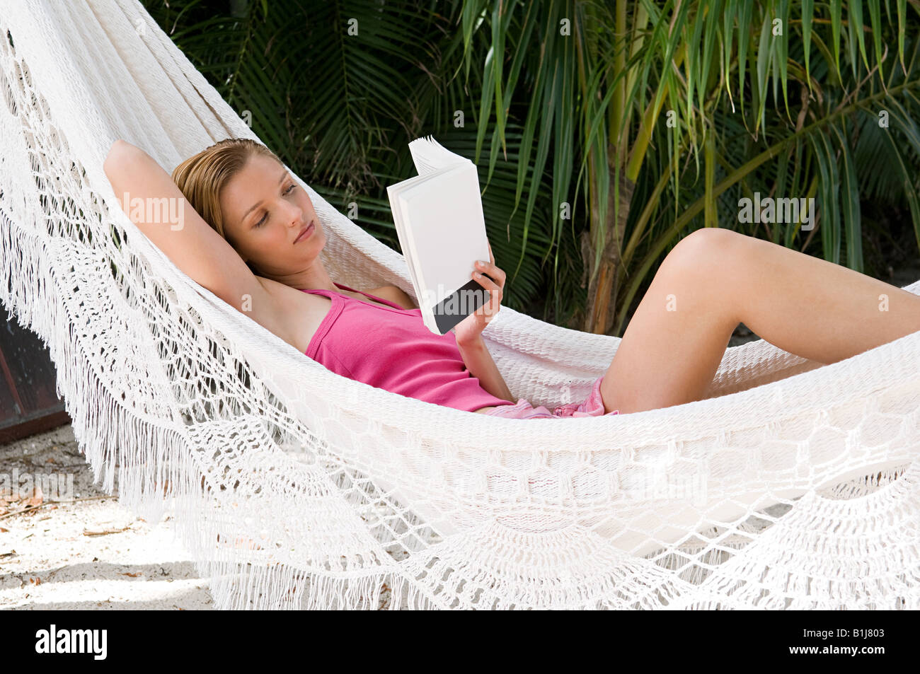 A woman in a hammock reading a book - Stock Image