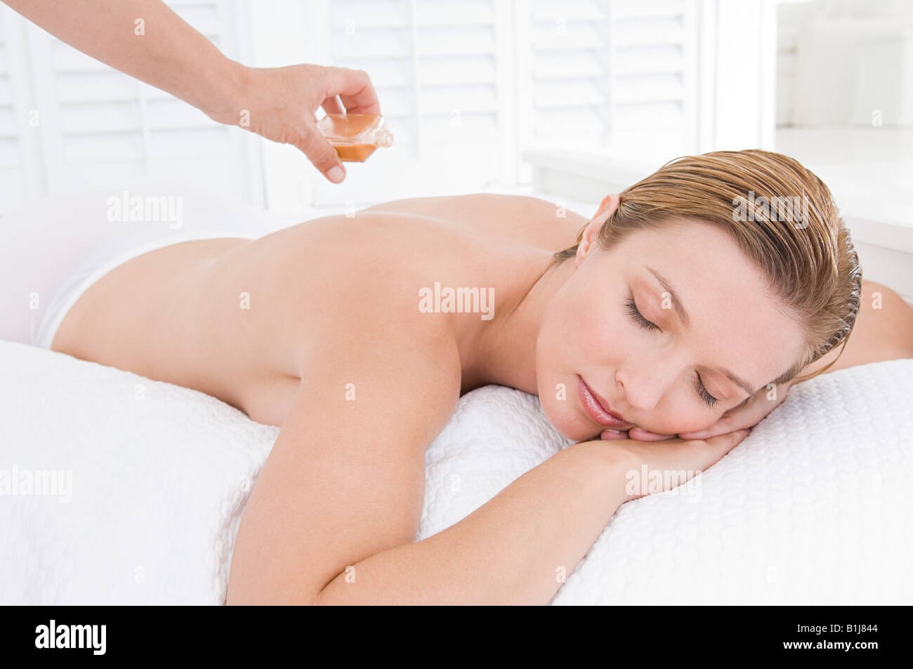 A masseuse applying oil to a womans back - Stock Image