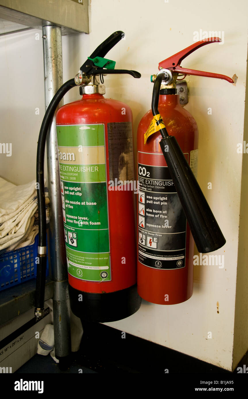 Safety equipment: two red fire extinguishers one foam one carbon ...