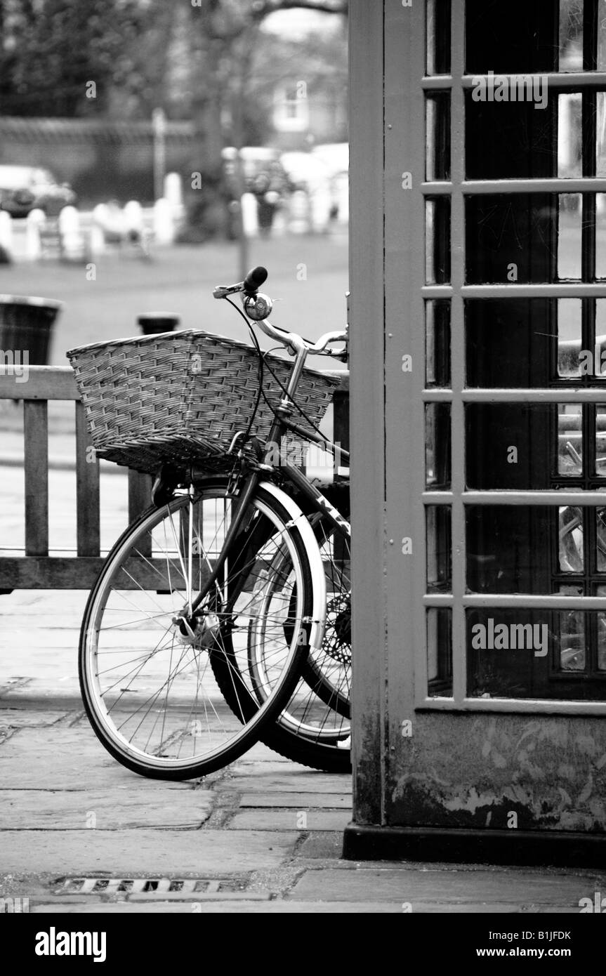 black and white image of bicycles parked next to a telephone booth, Richmond Green, Richmond, Surrey, England - Stock Image