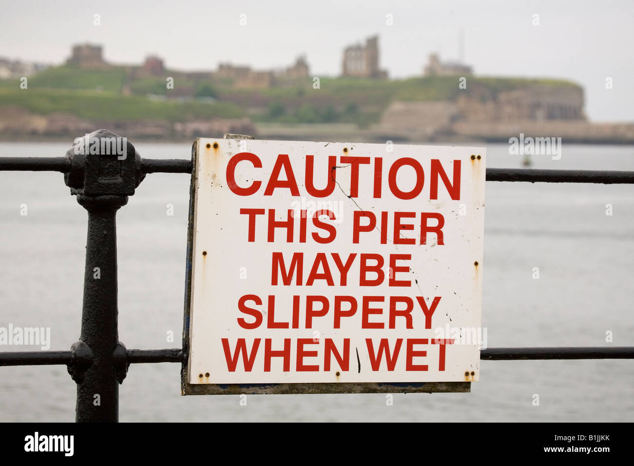 A sign warns that the pier may be slippery when wet in South Shields, England. - Stock Image