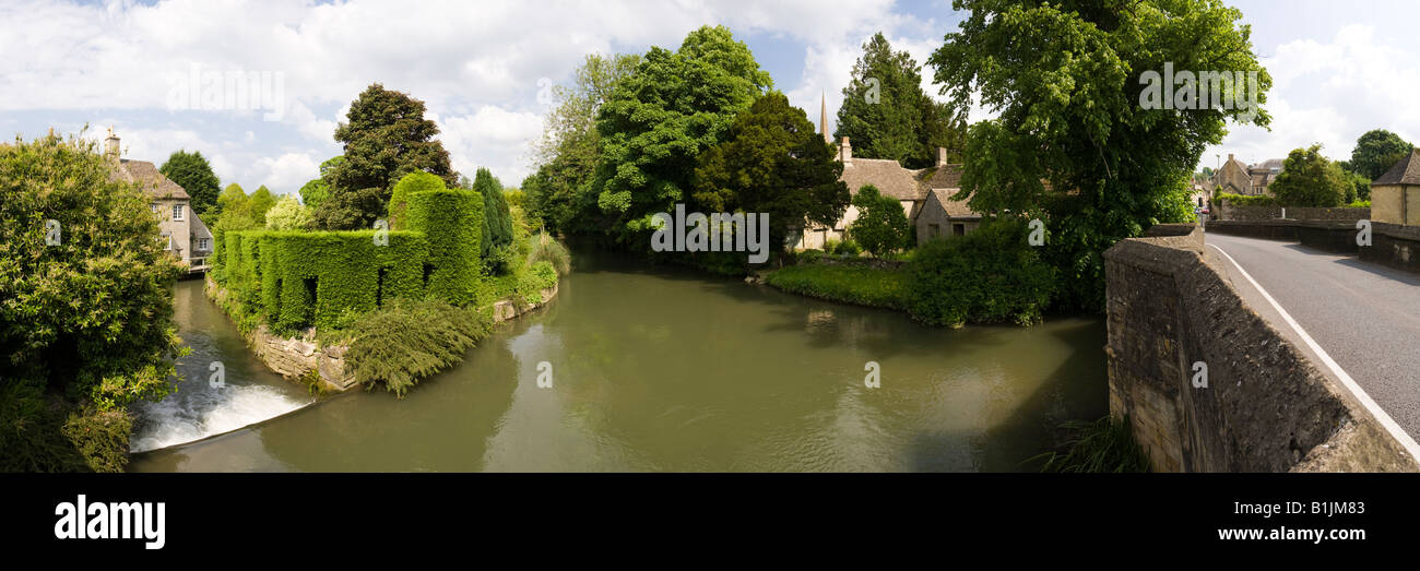 A panoramic view of the River Windrush flowing under the bridge in the Cotswold town of Burford, Oxfordshire - Stock Image