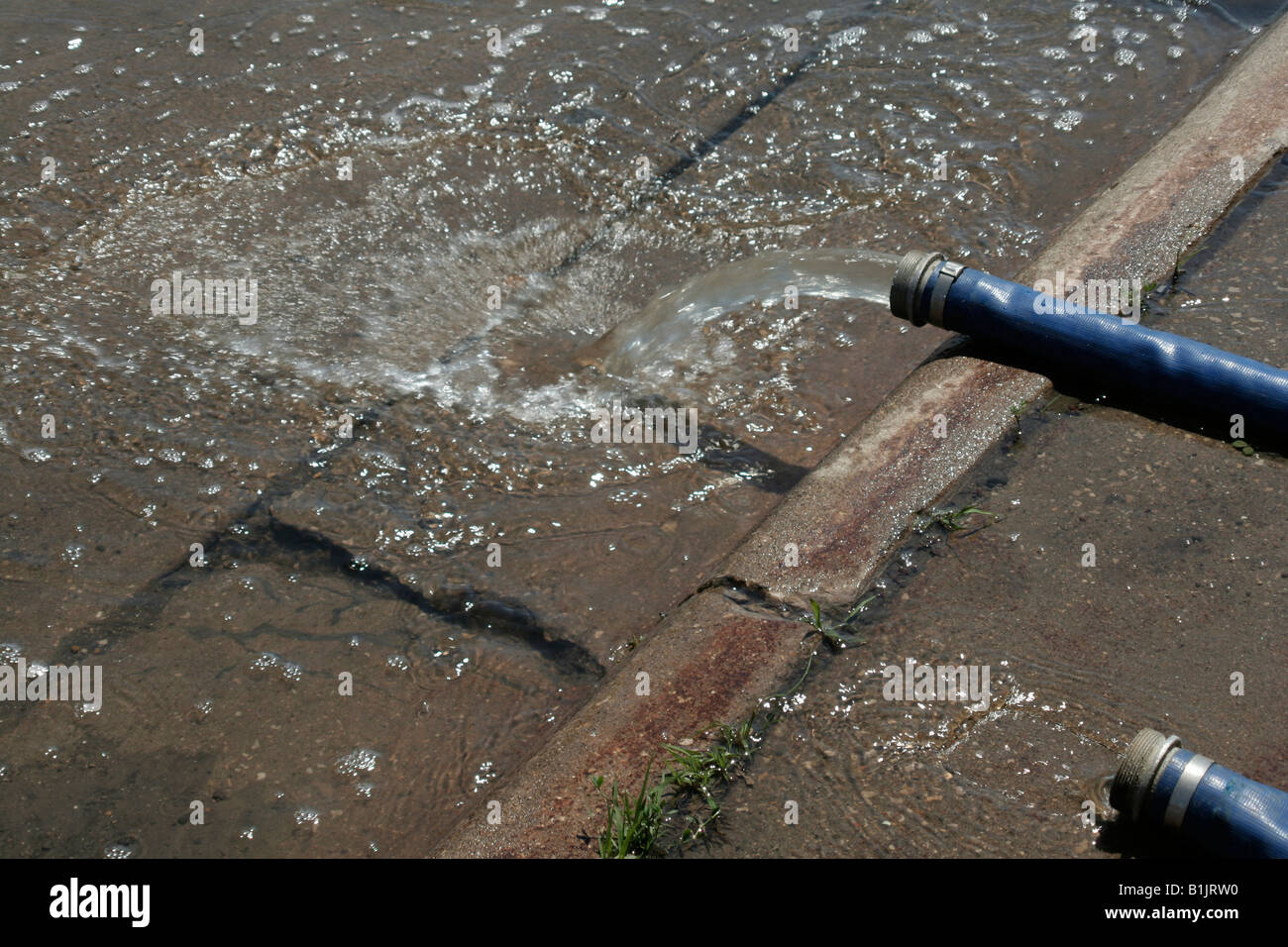 Hosepipes empty into street after flooding - Stock Image