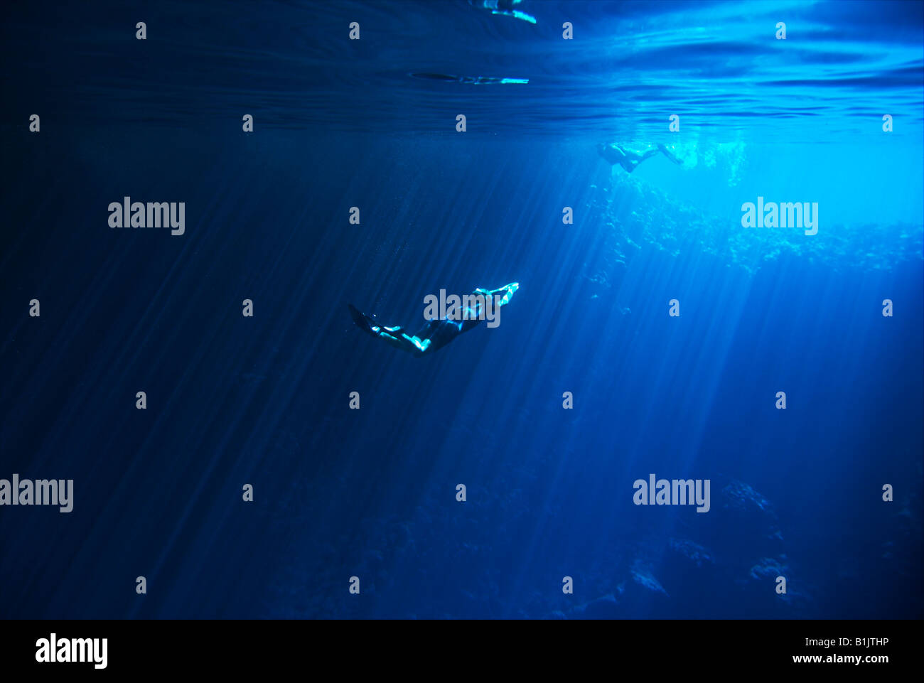Young Man swimming towards the light in underwater cave Tonga - Stock Image