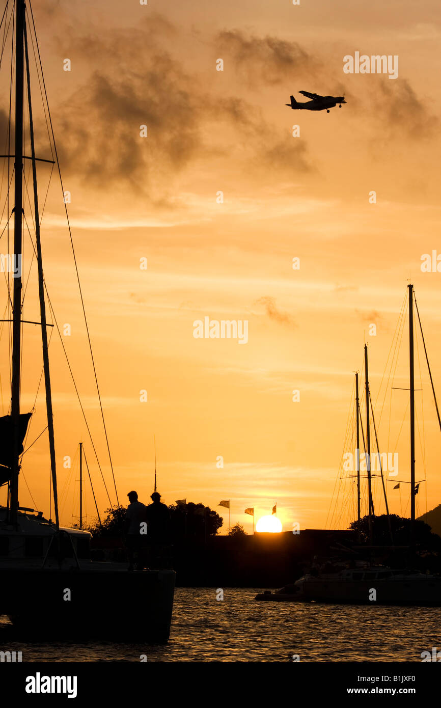 sailing yacht at anchor at sunset in the tropics with overflying aircraft - Stock Image