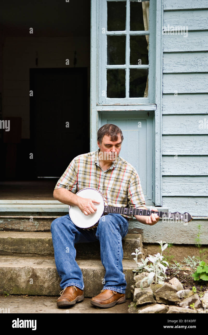 Banjo Player Sitting on the Steps of the Apothecary in the Pioneer Village of Spring Mill State Park Near Mitchell - Stock Image
