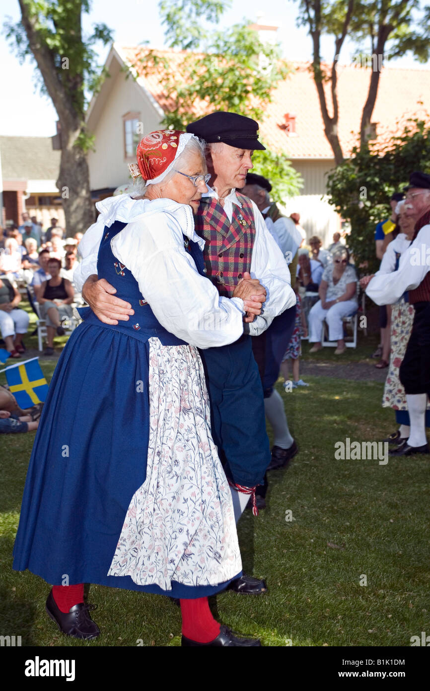 Elderly couple performs folk dance in traditional dresses during celebration of Swedish National Day - Stock Image