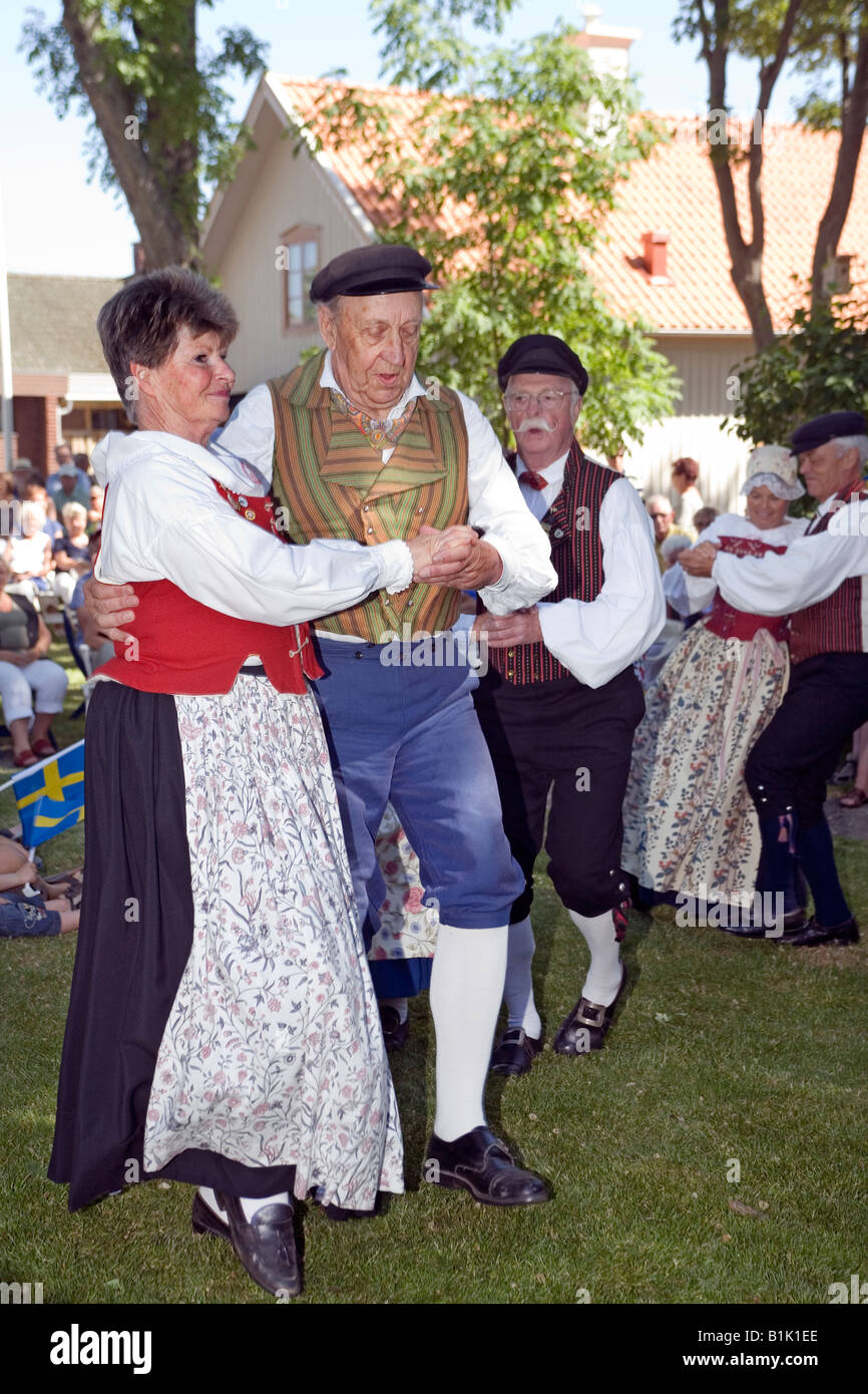 Elderly couple perform folk dance in traditional dresses during celebration of Swedish National Day Stock Photo
