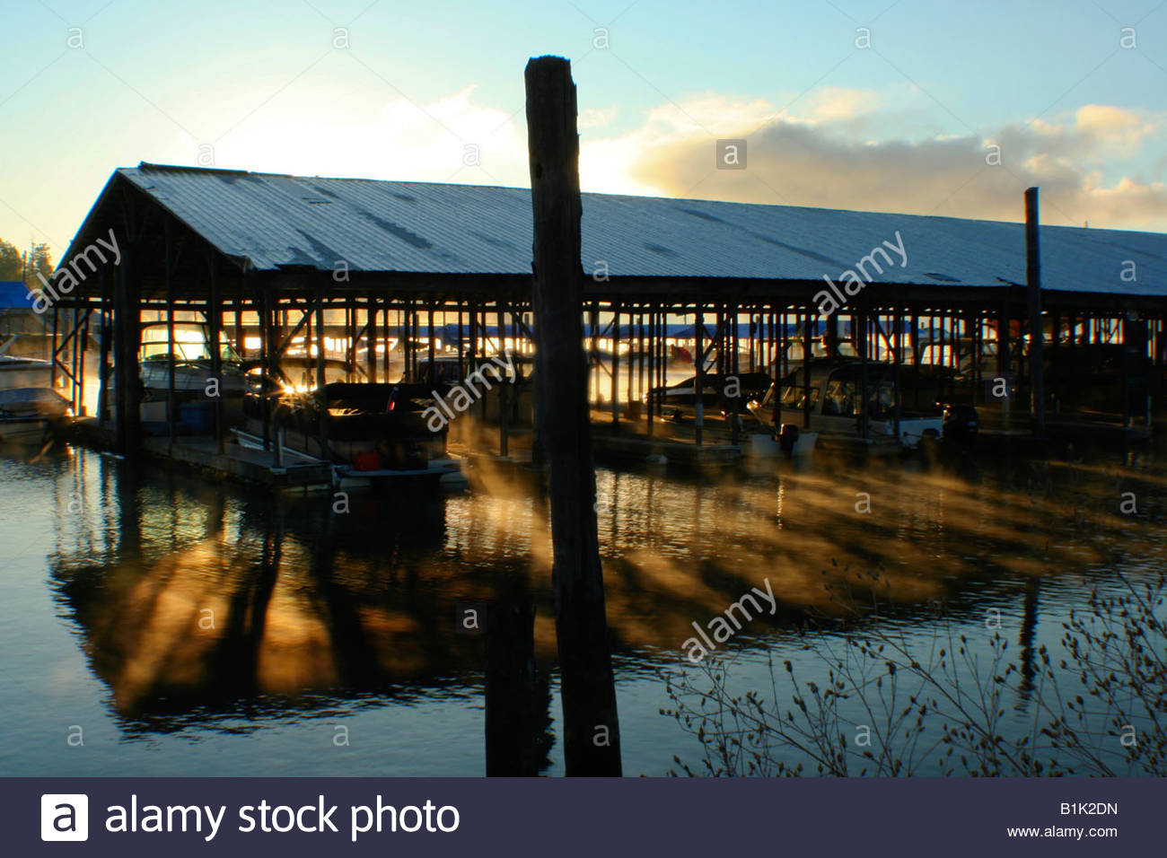Sunlight shines through a covered marina and reflects off the water on a early winter morning. - Stock Image