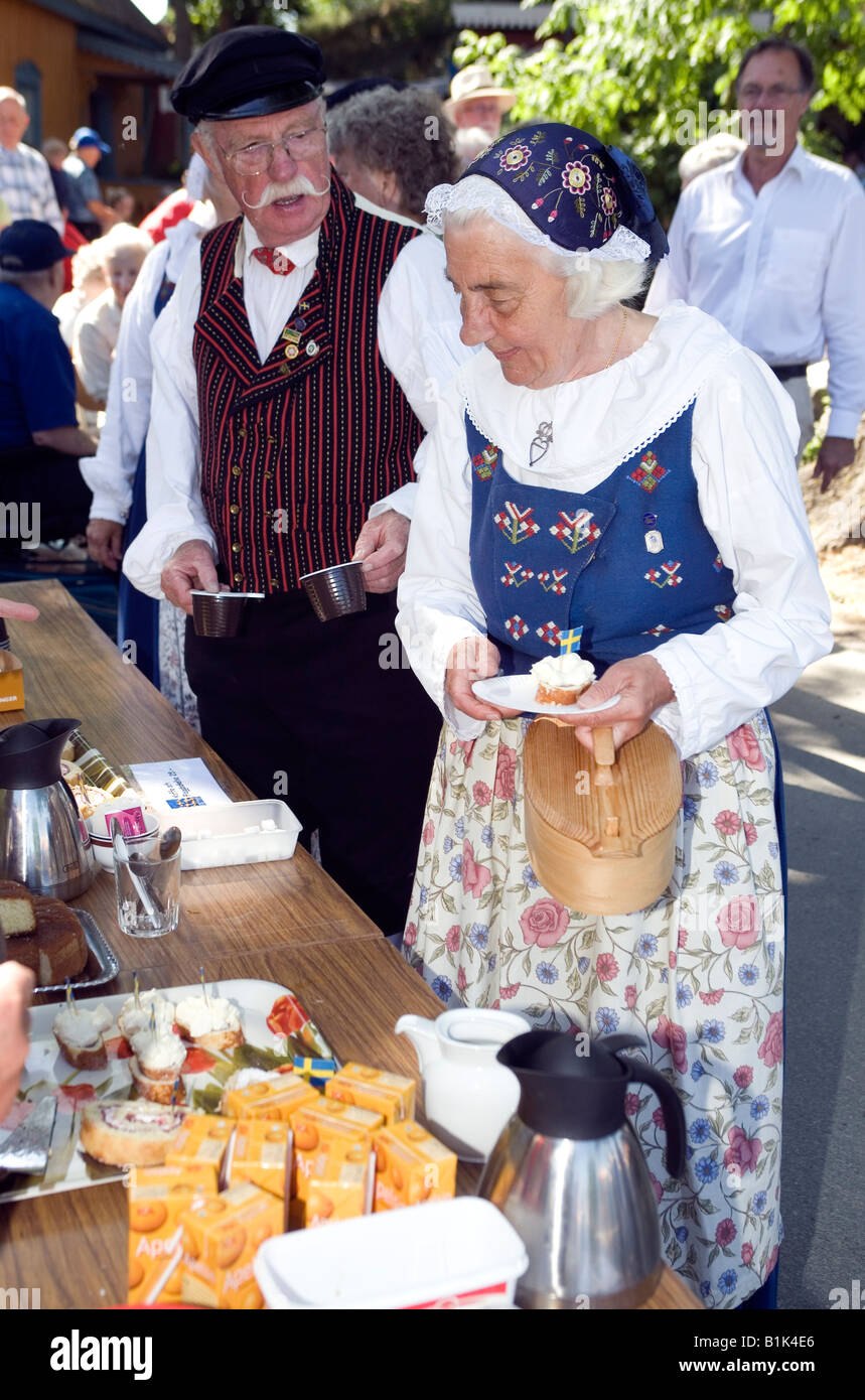 Elderly couple in traditional folk dress serving themselves at open air party at Öckerö island in Bohuslan West Stock Photo
