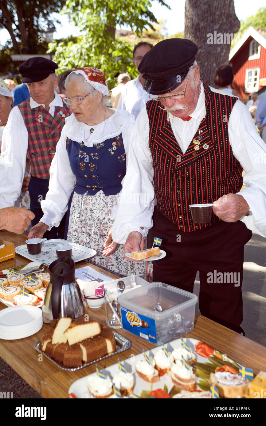 Senior citizens in traditional folk dress serving themselves at garden party at Öckerö island Bohuslan - Stock Image